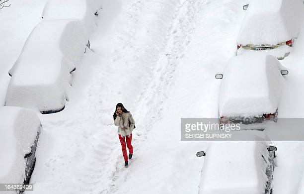 A girl walks in the street after a heavy snow storm in the Ukrainian capital of Kiev on March 23 2013 Kiev administration declared a state of...