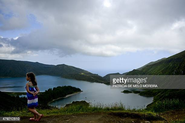 A girl walks near the Fire Lagoon on the Sao Miguel island in Azores on July 1 2015 AFP PHOTO/ PATRICIA DE MELO MOREIRA