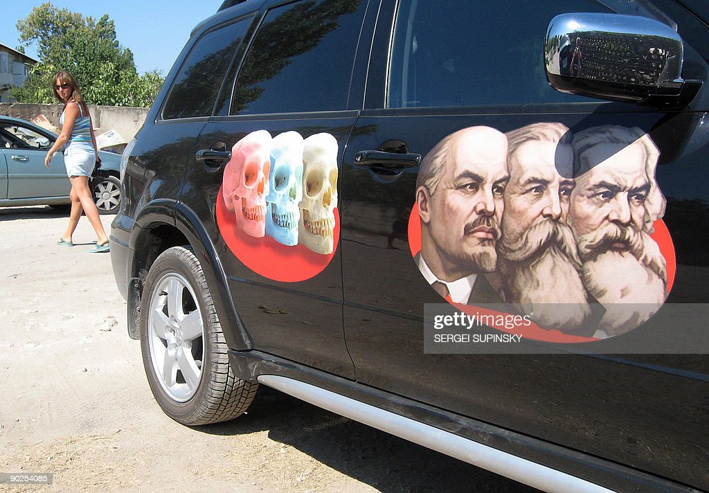 A girl walks past a car with stickers of skulls and portraits of Russians (From L) Vladimir Lenin, Karl Marx and Friedrich Engels in Sevastopol, the main base of the Russian Black Sea fleet on August 25, 2009.