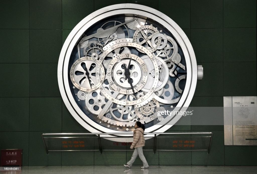 A girl walks past a model of a watch at a museum in Beijing on February 1 , 2013. Manufacturing activity in China expanded in January, two separate surveys showed on February 1, but they differed on whether the recovery was slowing or accelerating. AFP PHOTO / WANG ZHAO