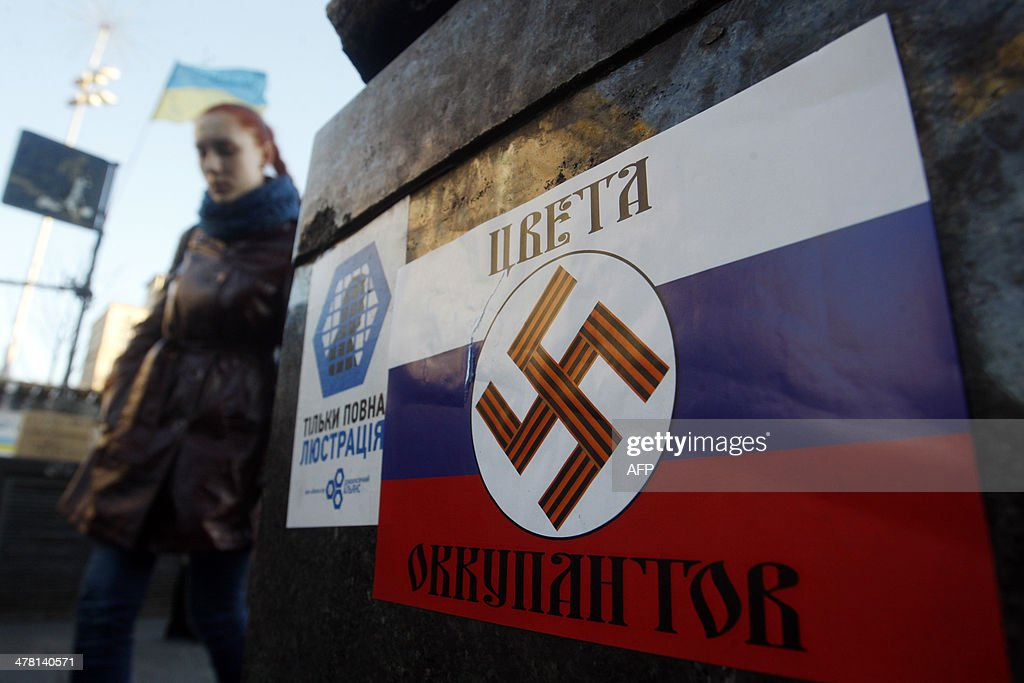 A girl walks past a poster with a Nazi swastika printed on a Russian flag and reading 'The colours of the occupiers' glued on Independence Square in Kiev on March 12, 2014. Russia will mirror any visa sanctions the European Union imposes on its lawmakers, a senior parliamentarian said Wednesday, as Moscow and the West slug it out diplomatically over the crisis in Ukraine.