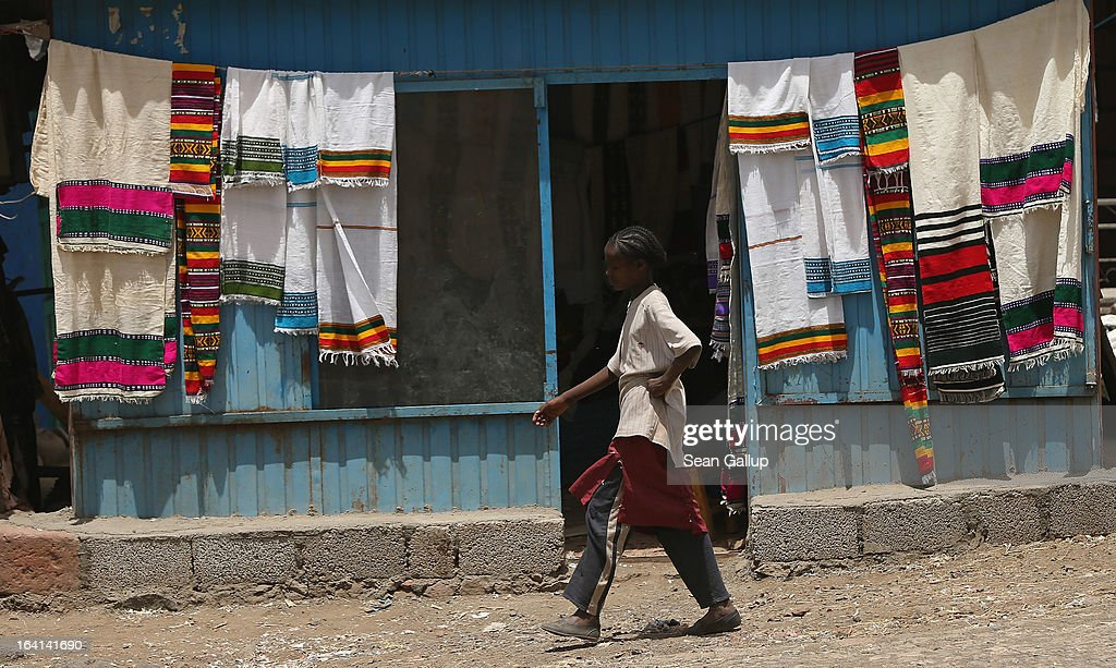 A girl walks past a shop selling traditional textiles near the Lalibela holy sites on March 19, 2013 in Lalibela, Ethiopia. Lalibela is among Ethiopia's holiest of cities and is distinguished by its 11 churches hewn into solid rock that date back to the 12th century. Ethiopia, with an estimated 91 million inhabitants, is the second most populated country in Africa and the per capita income is $1,200.