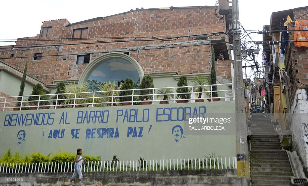 A girl walks past a wall with an inscription reading 'Welcome to the Pablo Escobar neighborhood. Here we breathe peace!' at Pablo Escobar neighborhood, on November 24, 2013 in Medellin, Antioquia department, Colombia. December 2, 2013 marks the 20th anniversary Escobar's death. AFP PHOTO/Raul ARBOLEDA