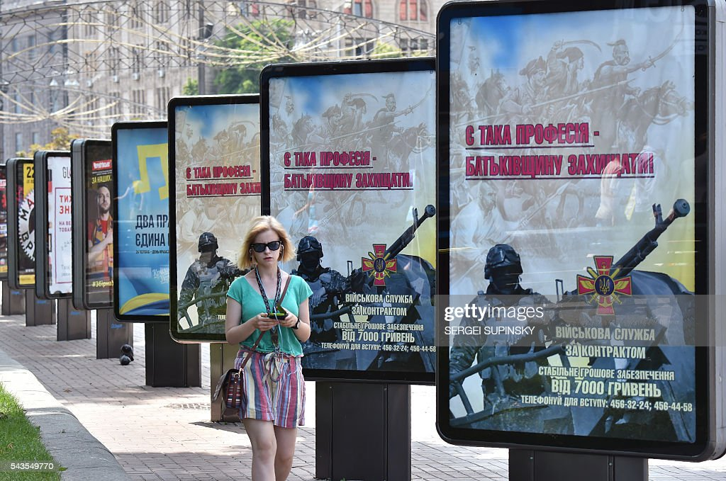 A girl walks past advertising billboards of Ukrainian Military Forces reading 'There is such a profession to defend the homeland', set in the centre of Kiev on June 29, 2016. A Ukrainian opera singer who performed for two decades in France before joining Kiev's volunteer forces fighting pro-Russian insurgents has been killed in the separatist east, officials said on June 29. / AFP / Sergei SUPINSKY