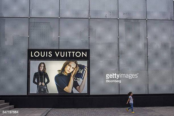 A girl walks past an advertisement for LVMH Moet Hennessy Louis Vuitton SA products in Ulaanbaatar Mongolia on Wednesday July 13 2016 The nation's...
