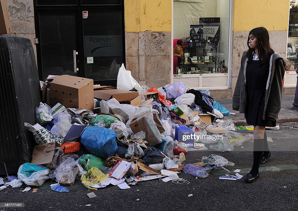 A girl walks past bins overflowing with rubbish in the city centre on November 12, 2013 in Madrid, Spain. Street cleaners, garbage collectors and public park gardeners working for Madrid city council started an indefinite strike six days ago after the private contracters plan to axe more than 1,000 jobs and introduce a 40% pay cut for the remaining workers.