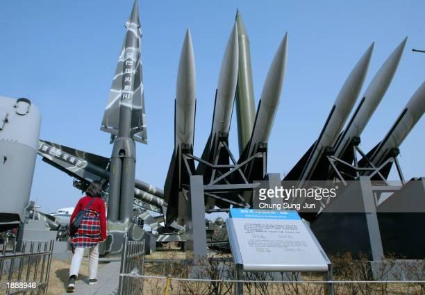 A girl walks past by North Korean and South Korean missiles at the Korea War Memorial Museum April 1 2003 in Seoul South Korea According to...