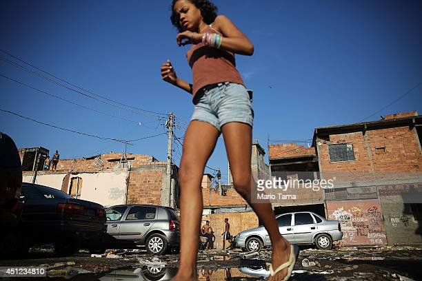 A girl walks past cars parked by World Cup tourists for a fee in the Metro Mangueira favela located 750 meters from Maracana stadium where Ecuador...