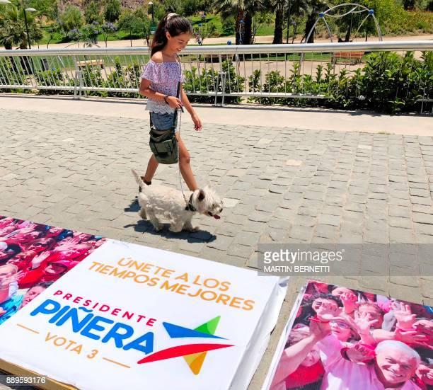 A girl walks past electoral propaganda of Chilean presidential candidate Sebastian Pinera in Santiago on December 10 2017 Conservative billionaire...