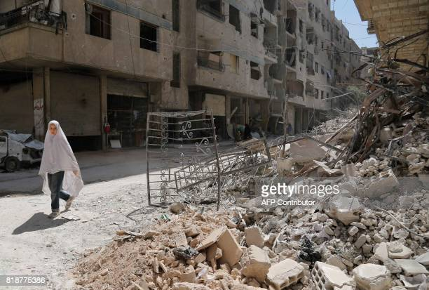 TOPSHOT A girl walks past the rubble of a destroyed building down a street in the rebelheld Syrian town of Ayn Tarma in the Ghouta area east of the...