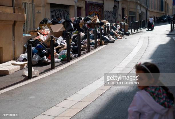 A girl walks past uncollected trash during a strike by refuse collectors on October 18 in Marseille southern France / AFP PHOTO / BERTRAND LANGLOIS