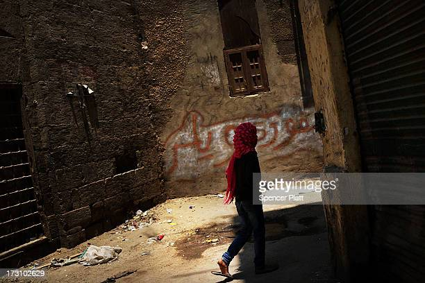 A girl walks through a street in a working class neighborhood in Cairo on July 7 2013 in Cairo Egypt Egypt continues to be in a state of political...