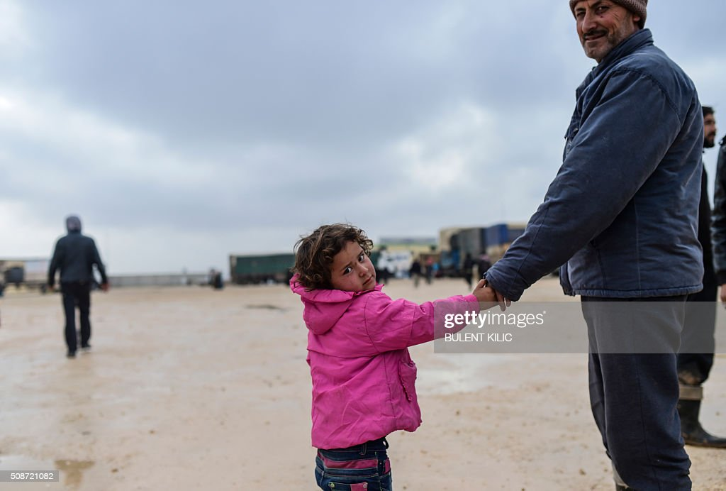 A girl walks with her father as Syrians fleeing the northern embattled city of Aleppo wait on February 6, 2016 in Bab al-Salam, near the city of Azaz, northern Syria, near the Turkish border crossing. Thousands of Syrians were braving cold and rain at the Turkish border Saturday after fleeing a Russian-backed regime offensive on Aleppo that threatens a fresh humanitarian disaster in the country's second city. Around 40,000 civilians have fled their homes over the regime offensive, according to the Syrian Observatory for Human Rights monitor. / AFP / BULENT KILIC