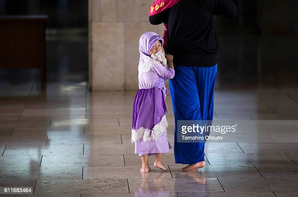 A girl walks with her mother at the Istiqlal Mosque on September 30 2016 in Jakarta Indonesia The world's fourth most populous nation and the largest...