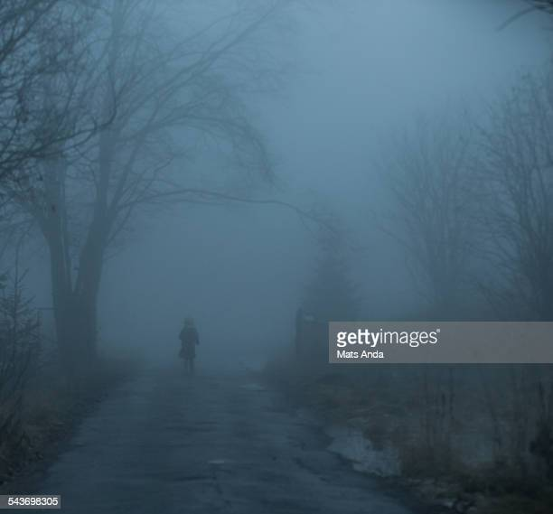 Girl wandering into fog on a scary night