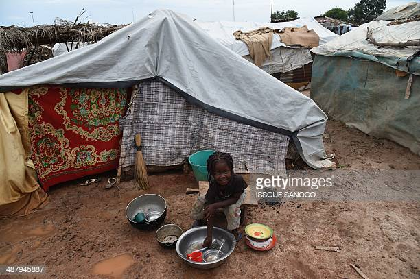 A girl washes dishes on May 3 2014 in the IDP camp near Bangui's Mpoko airport where the beginning of the rain season has worsensed the situation of...