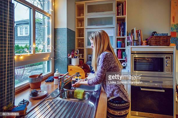 Girl washing hands in kitchen at dawn