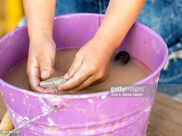 Girl washing her hands in a bucket of water