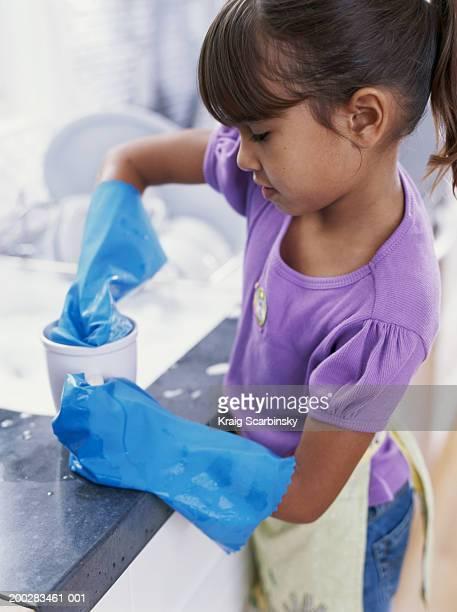 Girl (6-8) washing up at kitchen sink