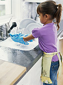 Girl (6-8) washing up at kitchen sink, side view