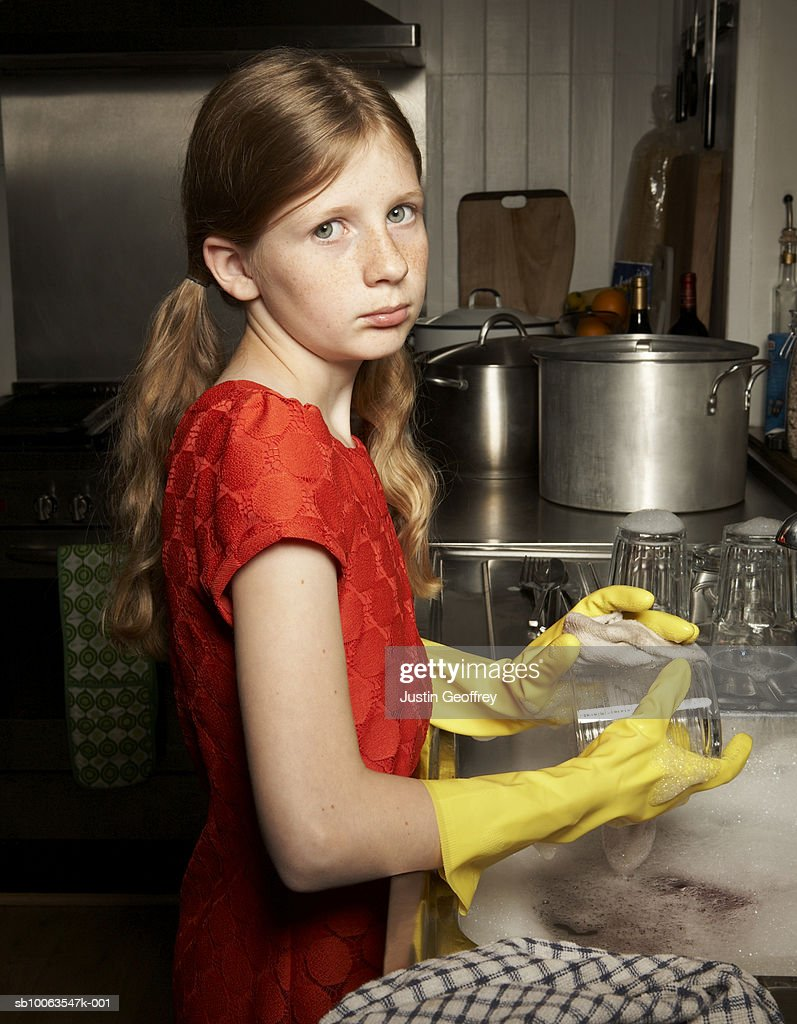 Girl (10-12) washing up at sink, portrait : Stock Photo
