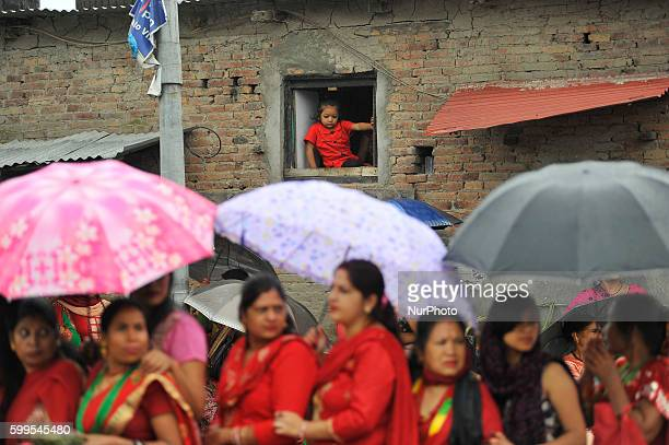 A girl watch from window as Hindu devotees lining to offer ritual prayer at the Rishishwor Mahadev Temple during Rishi Panchami Festival celebrations...