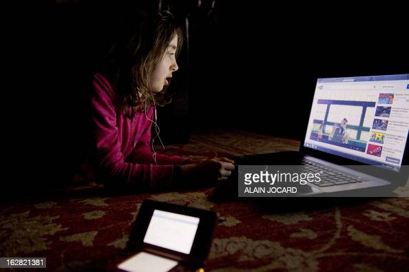 A girl watches a video on youtube on a computer on February 27 2013 in Chisseaux near Tours central France AFP PHOTO/ ALAIN JOCARD