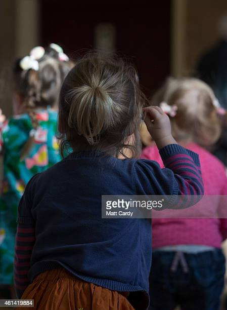 A girl watches as children dance at a playgroup for preschool aged children in Chilcompton near Radstock on January 6 2015 in Somerset England Along...