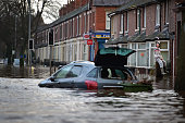 A girl watches rescue workers checking properties as teams continue to evacuate people from their homes after Storm Desmond caused flooding on...
