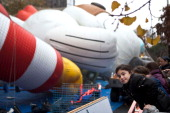A girl watches volunteers inflate a flotation during preparation for the Macy's Thanksgiving Day Parade on November 23 2011 on West 77th Street in...