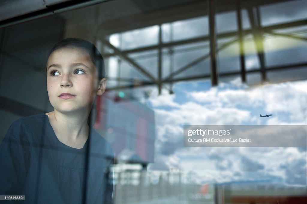 Girl watching airplane fly away : Stock Photo