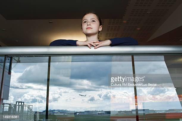 Girl watching airplane fly away