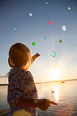 Girl watching balloons floating away