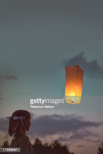 Girl watching floating sky lantern