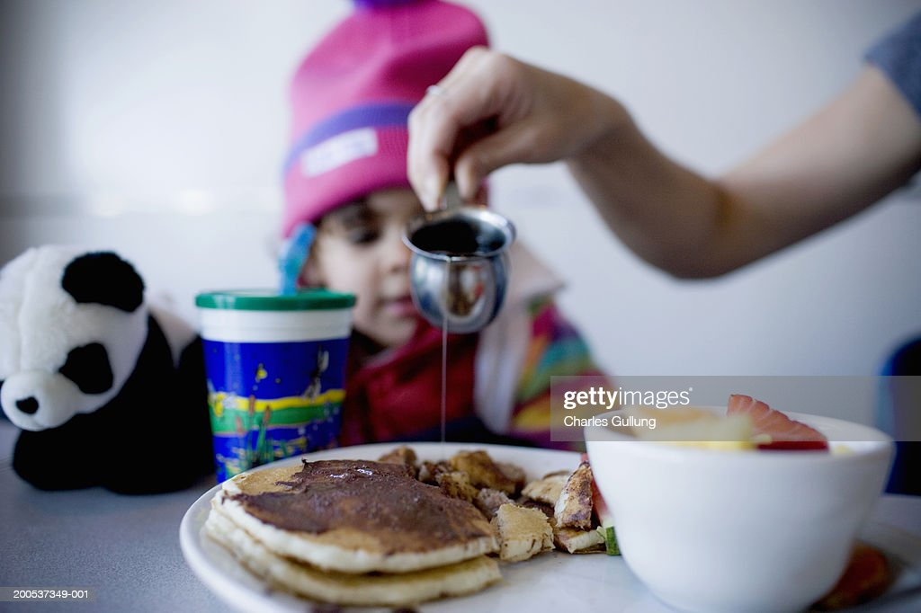 Girl (2-4) watching mother pour maple syrup on pancakes : Stock Photo