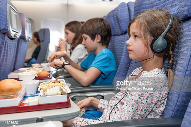 Girl watching movie on airplane, airline meal on tray table
