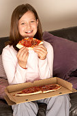 Girl watching television and eating pizza