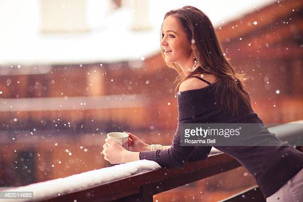 Girl watching the snowfall on chalet balcony