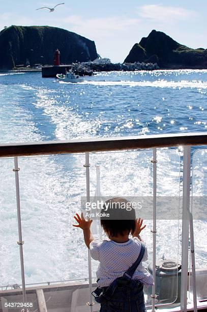 A girl watching the wake behind a sailing ship