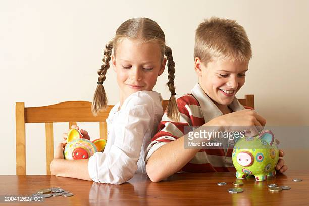 Girl (10-12) watching twin brother drop coin into piggy bank, smiling