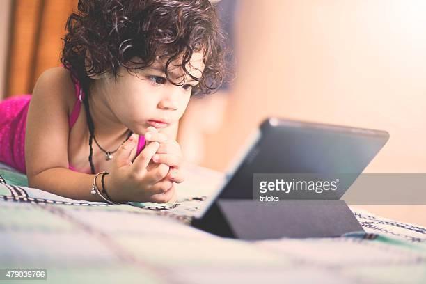 Rapariga ver vídeo com um tablet digital em casa