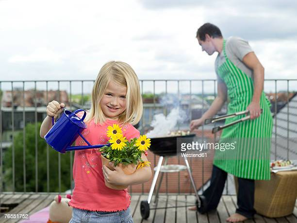 Girl (6-7) watering flowers, father cooking in background