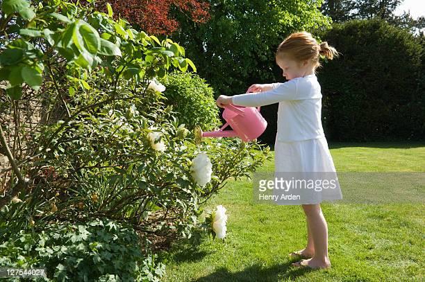 Mädchen gießen Blumen im Garten