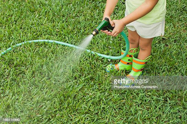 Girl watering lawn with garden hose, cropped