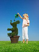 Girl (5-7) watering topiary