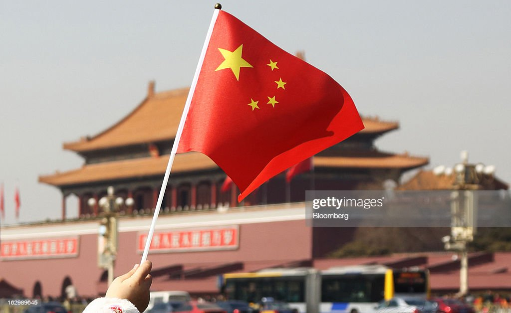 A girl waves a Chinese flag in front of Tiananmen Gate in Beijing, China, on Sunday, March 3, 2013. Premier Wen Jiabao will this week formally announce this year's economic targets when he delivers his final work report to the National People's Congress, which begins on March 5. Photographer: Tomohiro Ohsumi/Bloomberg via Getty Images