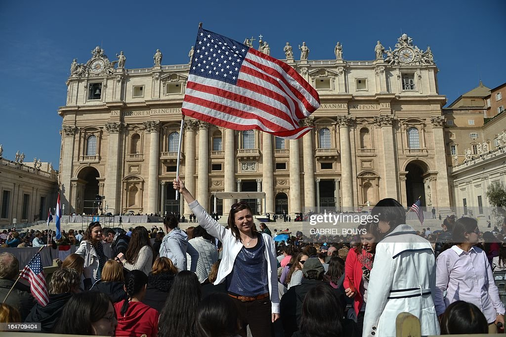 A girl waves a US national flag on March 27, 2013 at St Peter's square before a papal audience at the Vatican. AFP PHOTO / GABRIEL BOUYS
