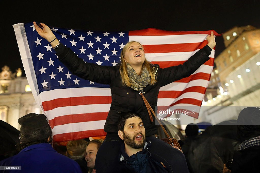 A girl waves an American flag as she reacts before newly elected Pope Francis I appeared on the central balcony of St Peter's Basilica on March 13, 2013 in Vatican City, Vatican. Argentinian Cardinal Jorge Mario Bergoglio was elected as the 266th Pontiff and will lead the world's 1.2 billion Catholics.