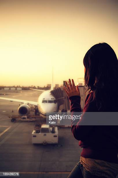 Girl waves at an airplane