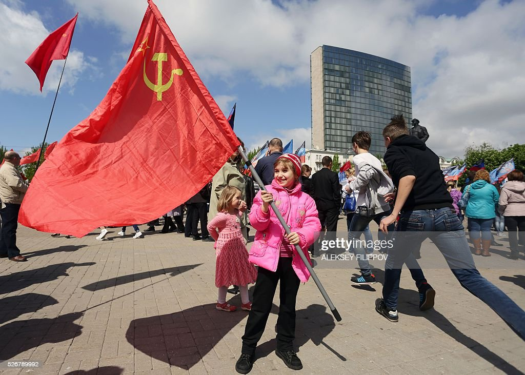 A girl waves the former USSR flag during a May Day rally organised by supporters of the self-proclaimed People's Republic of Donetsk in the centre of the eastern Ukrainian city of Donetsk on May 1, 2016. / AFP / Aleksey Filippov
